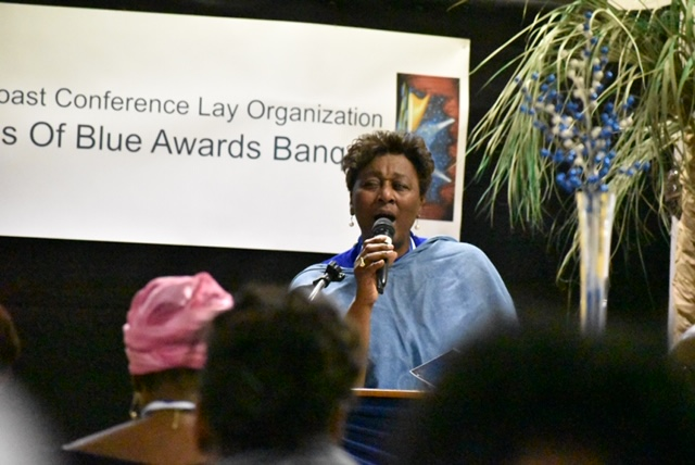 Eleventh Episcopal District Lay President Patricia Wright stand behind a podium to offer her final remarks at the Shades of Blue Awards Banquet on March 22, 2019.